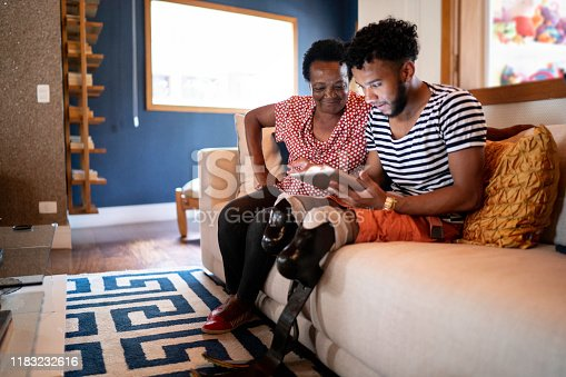 Son/Grandson using digital tablet with his mother/grandmother