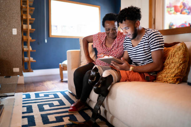 Son/Grandson using digital tablet with his mother/grandmother Son/Grandson using digital tablet with his mother/grandmother paraplegic stock pictures, royalty-free photos & images