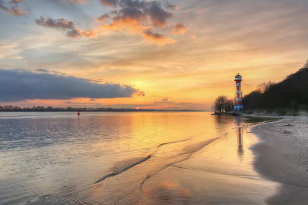 sonnenuntergang am leuchtturm an der elbe in hamburg - wasser stock pictures, royalty-free photos & images