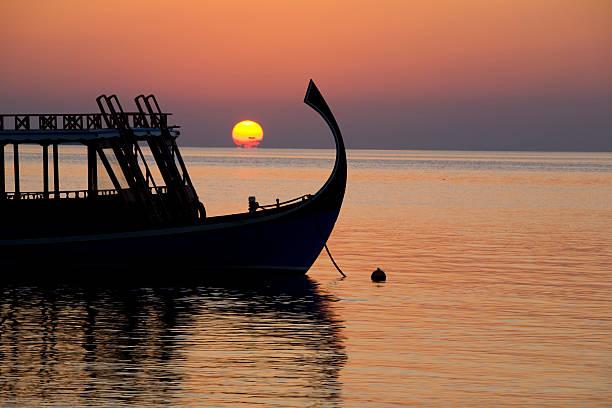 Sonnenuntergang mit Ausflugs-Dhoni stock photo