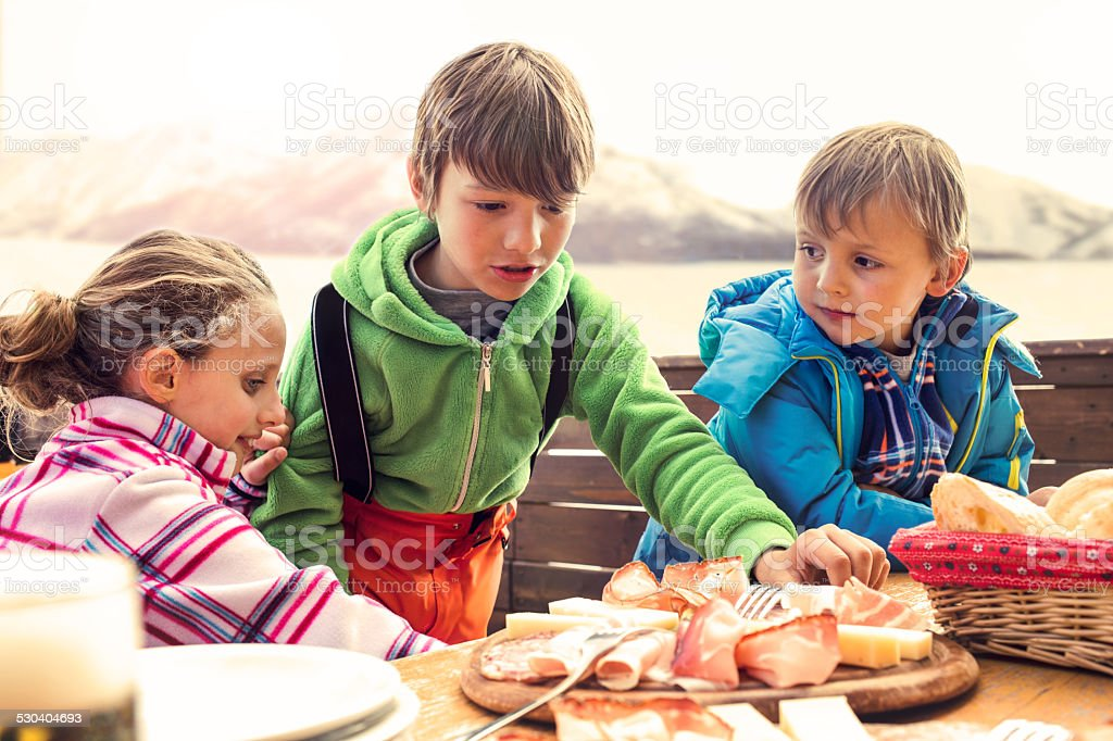 sons have lunch in chalet in the mountain stock photo