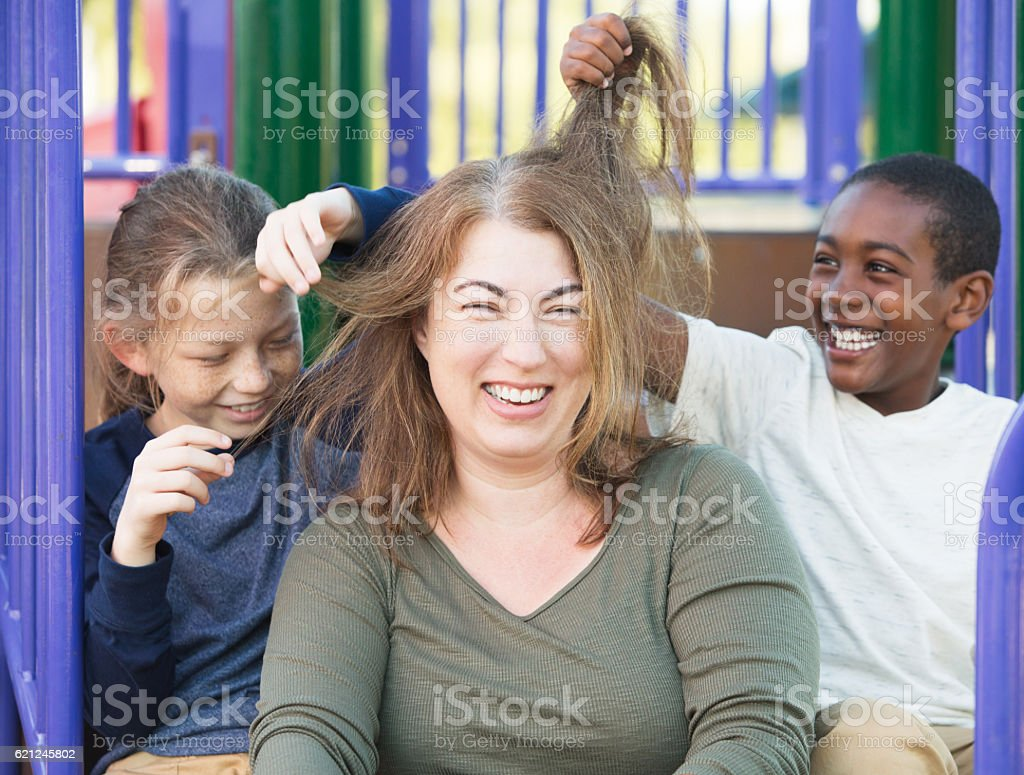 Sons playing with hair of mother stock photo