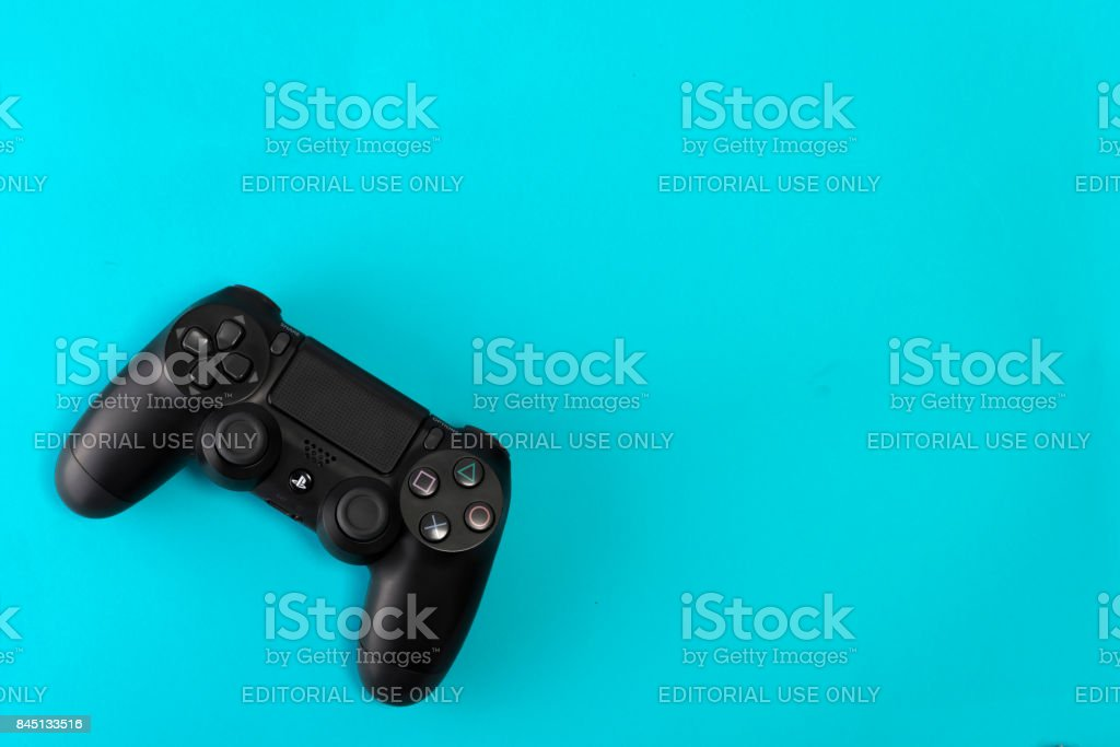 Sony PlayStation 4 Slim 1Tb revision and game controller on blue background stock photo