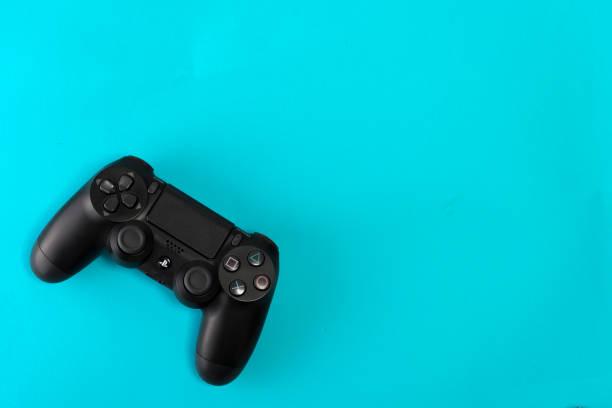 sony playstation 4 slim 1tb-herziening en game controller op blauwe achtergrond - playstation stockfoto's en -beelden