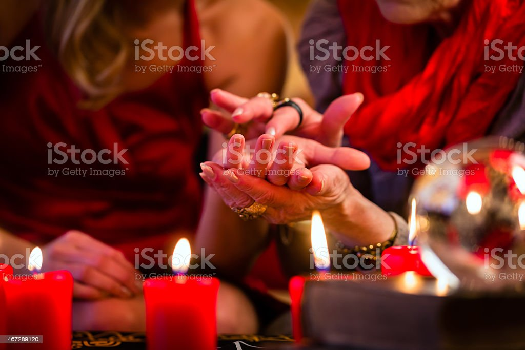 Soothsayer during session of palmistry over candles stock photo