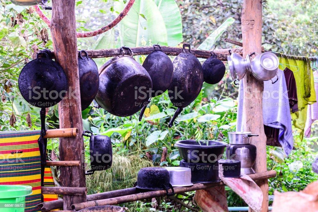 Sooty pots and pan hang on wooden bar at countryside. foto de stock royalty-free