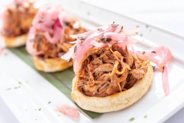 Sopes de Cochinita Pibil - Cochinita Pibil:is a Mexican slow-roasted pork dish from the Yucatán. Sopes: It is an antojito which is made from a circle of fried masa (ground maize soaked in lime) Sopes de cochinita pibil: Cochinita Pibil: is a traditional Mexican slow-roasted pork dish from the Yucatán Península. Sopes: It is an antojito which is made from a circle of fried masa (ground maize soaked in lime, also used as the basis for tamales and tortillas) with pinched sides spit roasted stock pictures, royalty-free photos & images
