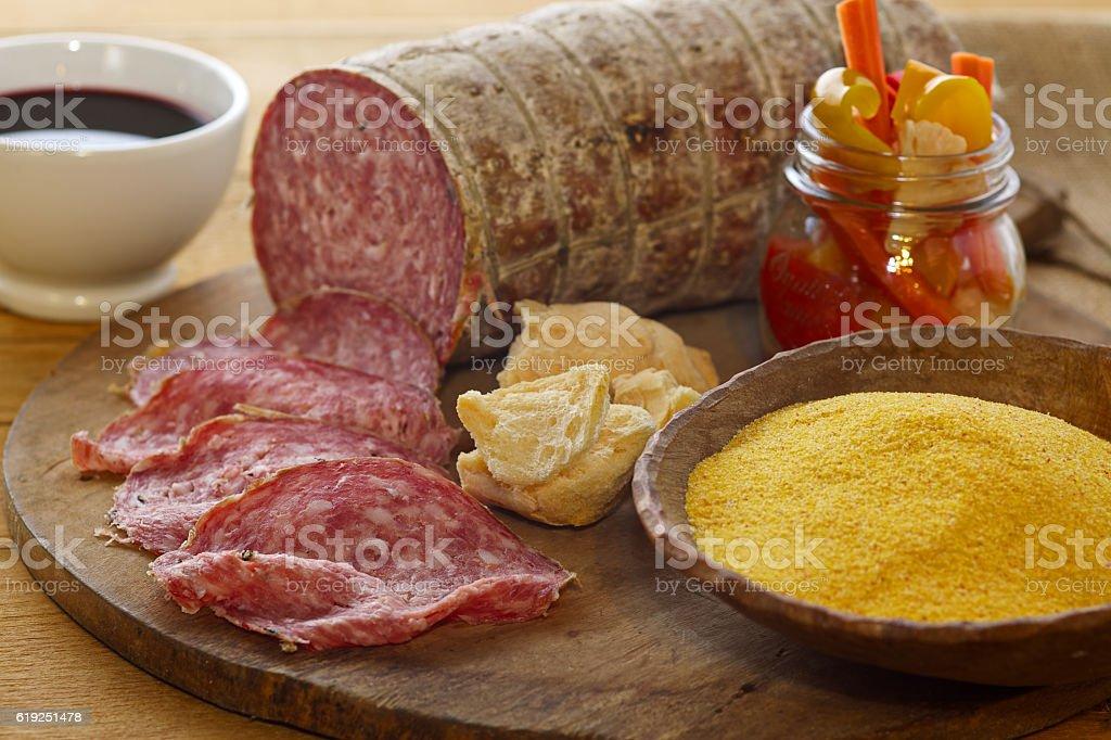 Sopressa, pickels,, corn powder and red wine composition stock photo