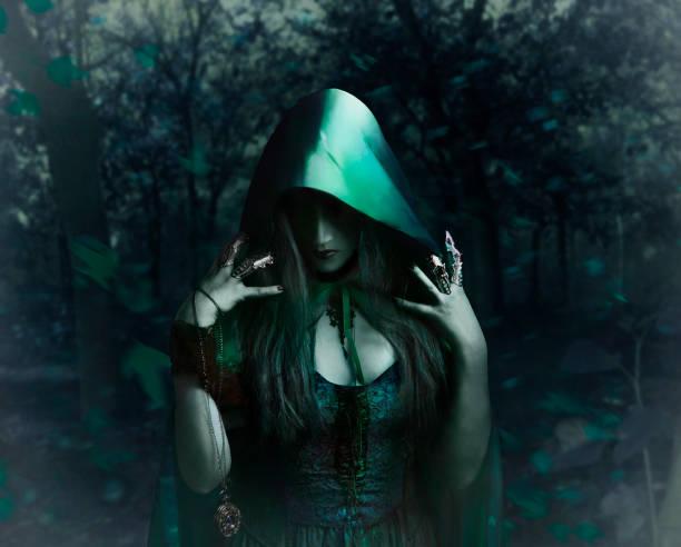 Bruja con capa verde en el bosque - foto de stock