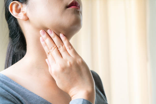 Sore Throat. Beautiful woman hand touching her pain neck. Woman healthcare concept stock photo
