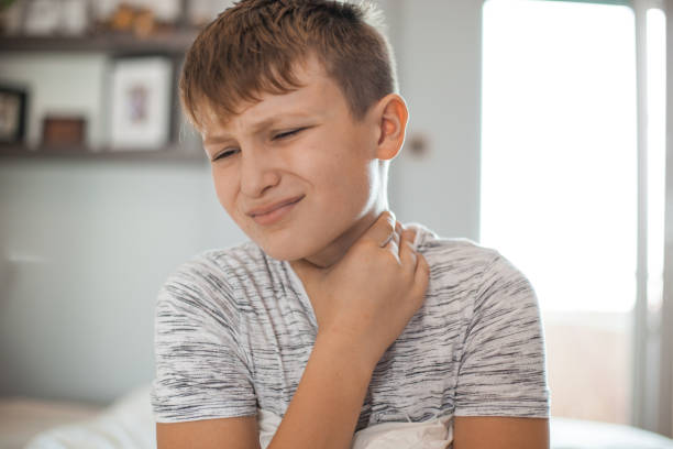 Sore Throat - Boy holding his neck in pain stock photo