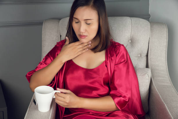 A sore throat is a pain, Scratchiness A sore throat is a pain, Scratchiness, or irritation, Asian women in red silk nightwear with acid reflux at night, The concept of healthcare and medicine. heartburn throat pain stock pictures, royalty-free photos & images