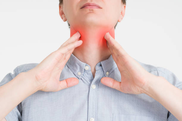 Sore throat, men with pain in neck, gray background stock photo