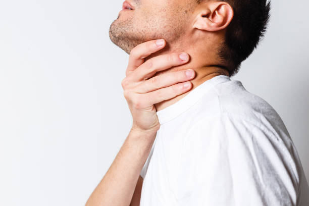 Sore throat of a men. Touching the neck. Red dot Sore throat of a men. Touching the neck. Red dot heartburn throat pain stock pictures, royalty-free photos & images