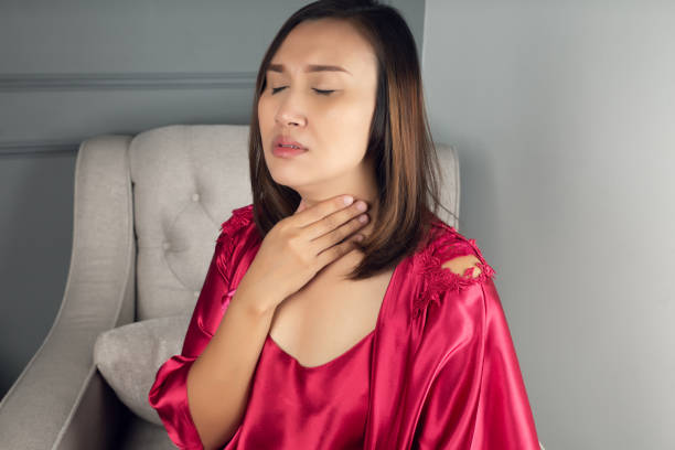 Sore throat pain symptoms. Throat infection. A woman wearing a satin nightgown and red robe suffering from hoarseness or laryngitis in the living room at night. Sore throat pain symptoms. Throat infection. A woman wearing a satin nightgown and red robe suffering from hoarseness or laryngitis in the living room at night. heartburn throat pain stock pictures, royalty-free photos & images