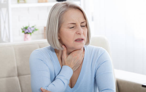 Sore throat woman at home. Sore throat woman. Concept photo with indicating location of the pain. heartburn throat pain stock pictures, royalty-free photos & images