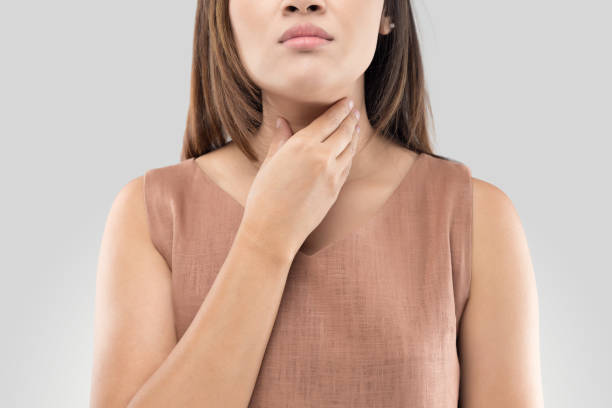 Sore throat woman on gray background stock photo