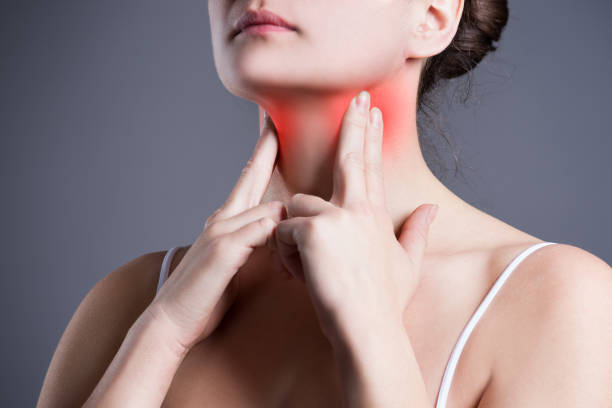Sore throat, woman with pain in neck, gray background stock photo