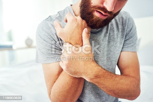 Cropped shot of a young man experiencing discomfort in his hands at home