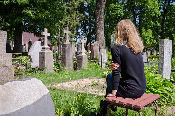 femme à la tristesse père mari tombe dans le cimetière - veuve photos et images de collection