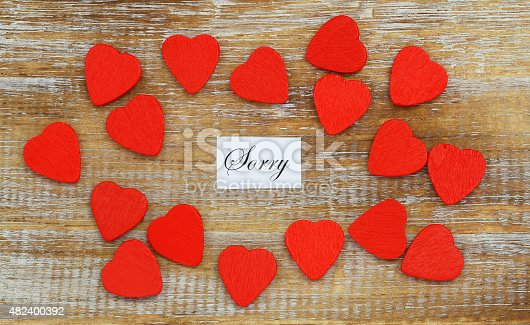 istock Sorry card with little red hearts scattered on rustic wood 482400392