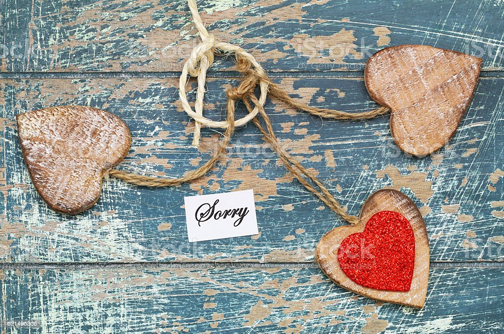 Sorry card with three wooden hearts on rustic surface Lizenzfreies stock-foto