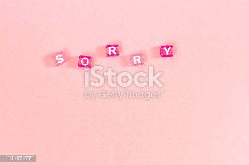 istock sorry  inscription made of colorful cube beads with letters. Festive pink background concept with copy space 1131871771
