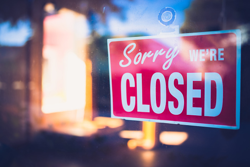 Red sign on window informing that the business is closed