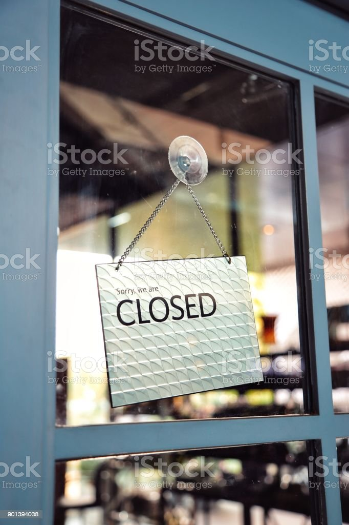 Sorry we are closed sign on the window blue door shop stock photo