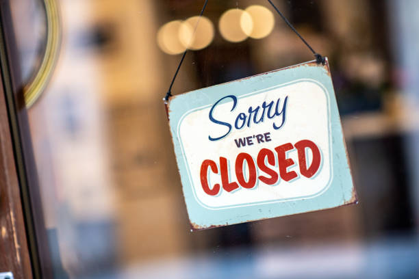 Sorry we're closed sign on store window door stock photo