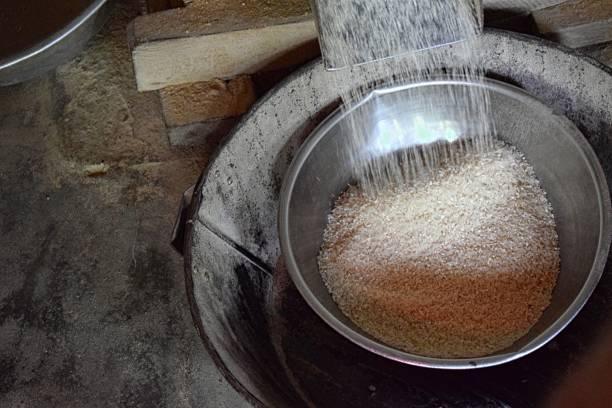 Sortie du riz après l'écorceuse Le riz récolté est nettoyé de ces impuretés en aspirant les brins d'herbe et la terre et en éliminant les pierres. Le rizon passe dans l'écorceuse, une machine, composée de deux rouleaux, crée exprès pour séparer l'écosse (balle) du riz. On obtient le riz en paille (riz complet). Afin d'obtenir le riz blanc, il faut le blanchir en faisant passer le riz complet entre deux pierres. riz stock pictures, royalty-free photos & images