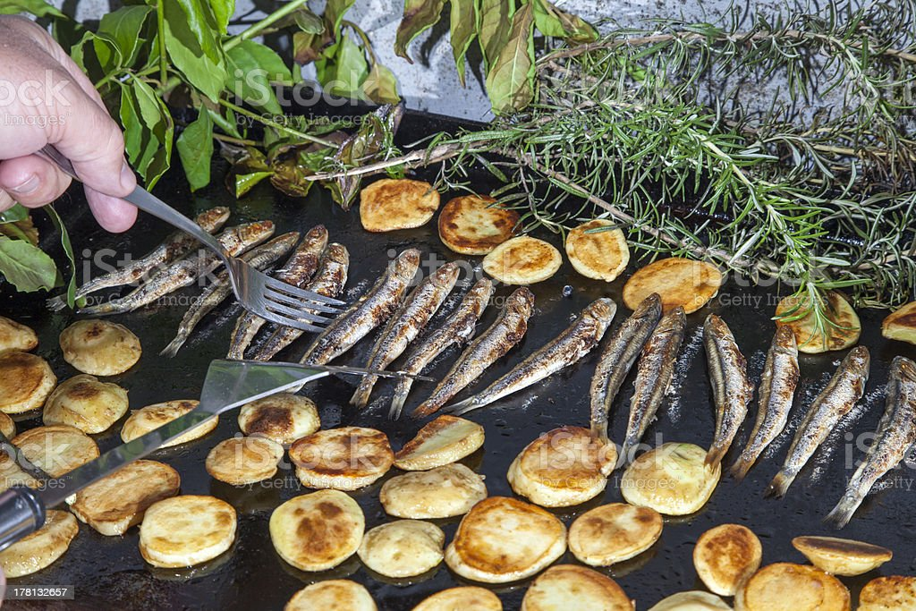 Sorting mackerel fishes with potatoes  on grill stock photo