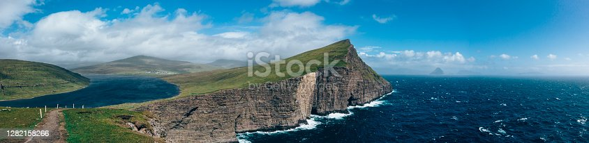 sorvagsvatn lake is the largest lake in the faroe islands, above the north atlantic ocean. aerial panorama coastal view towards the rocky faroese coastline of vagar - vágar island, bosdalafossur waterfall and trælanípa slave cliff. vágar island, faroe islands, denmark, nordic countries, europe