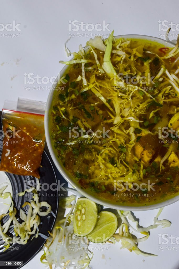 soto ayam traditional food of Surabaya, Indonesia. with bean sprouts, lime, and messy noodles. stock photo