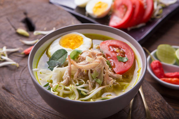 Soto: Indonesian chicken soup with hard boiled eggs, tomato, bean sprout, lemon, cayenne pepper on rustic brown wooden background stock photo
