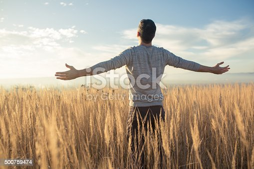 Young caucasian man standing in the middle of a prairie with his arms outstretched, enjoying a beautiful sunny day in the nature.