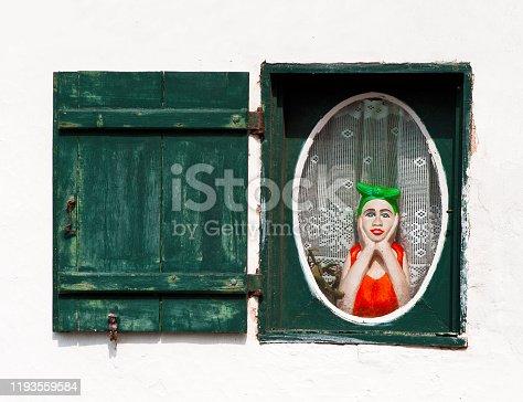 Une figurine placée derrière une fenêtre de maison semble bien pensive...