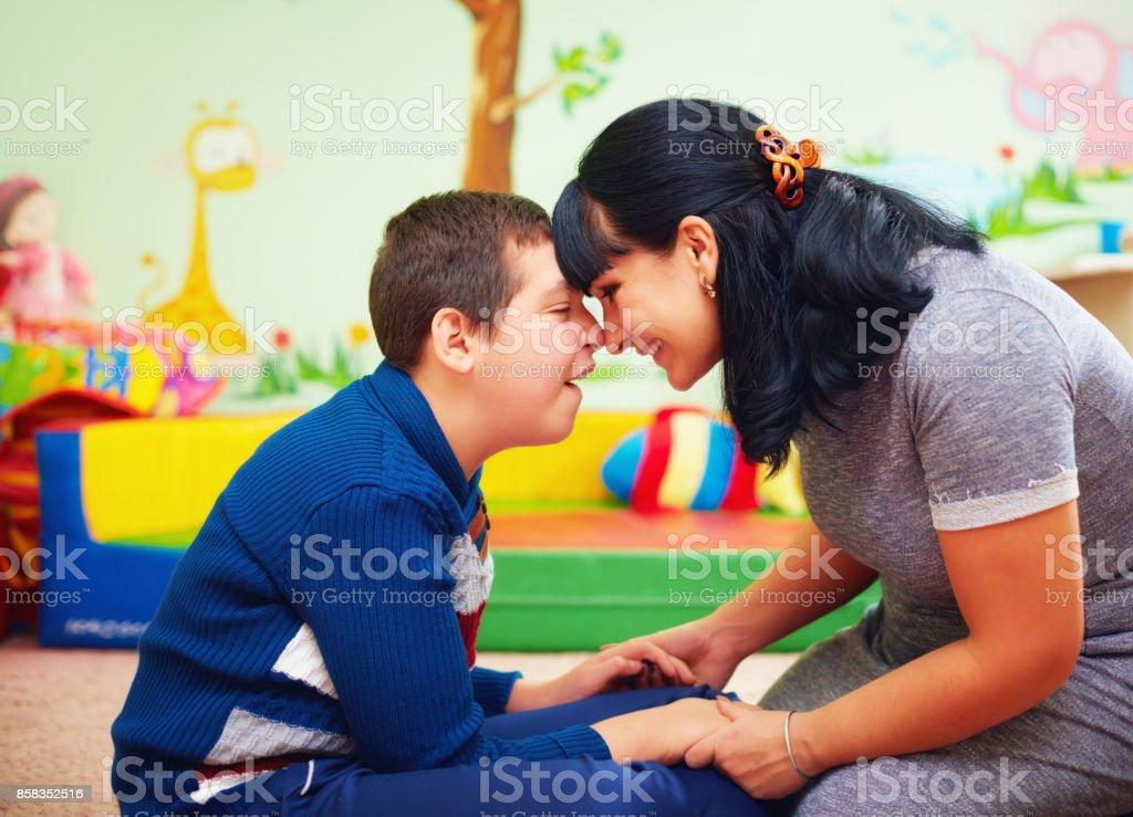 gefühlvolle Zeit. Porträt der Mutter und ihres geliebten Sohnes mit Behinderung im Reha-Zentrum – Foto