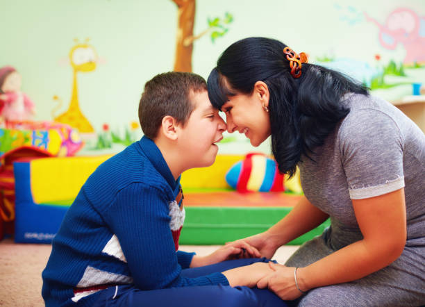 soulful moment. portrait of mother and her beloved son with disability in rehabilitation center - handicapped imagens e fotografias de stock