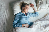Beautiful happy Caucasian woman in blue pyjamas sleeping on a king-size bed.