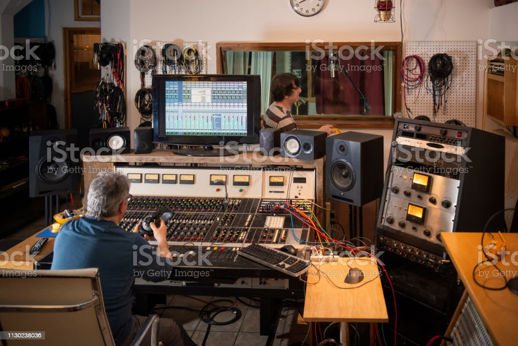 Sound Engineer and Musician Preparing for Recording Session in Studio