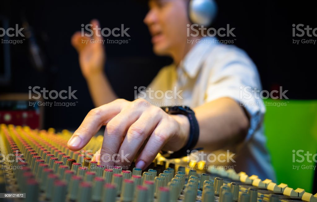 sound engineer hands working on audio mixing console in recording, broadcasting studio stock photo