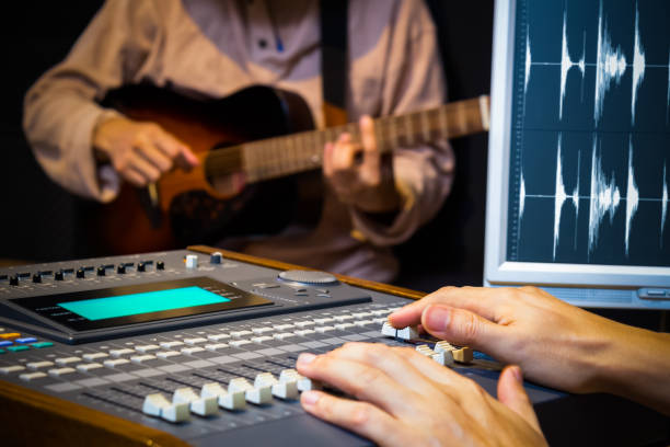 sound engineer hands working on digital sound mixer for acoustic guitar recording in music studio stock photo