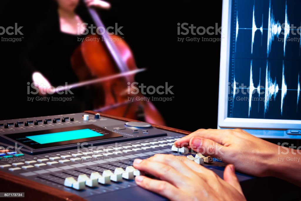 sound engineer hands working on digital sound mixer for cello recording stock photo