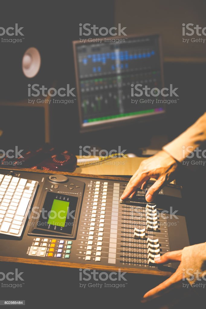 sound engineer hands working on digital sound mixer in recording, broadcasting, post production studio. stock photo