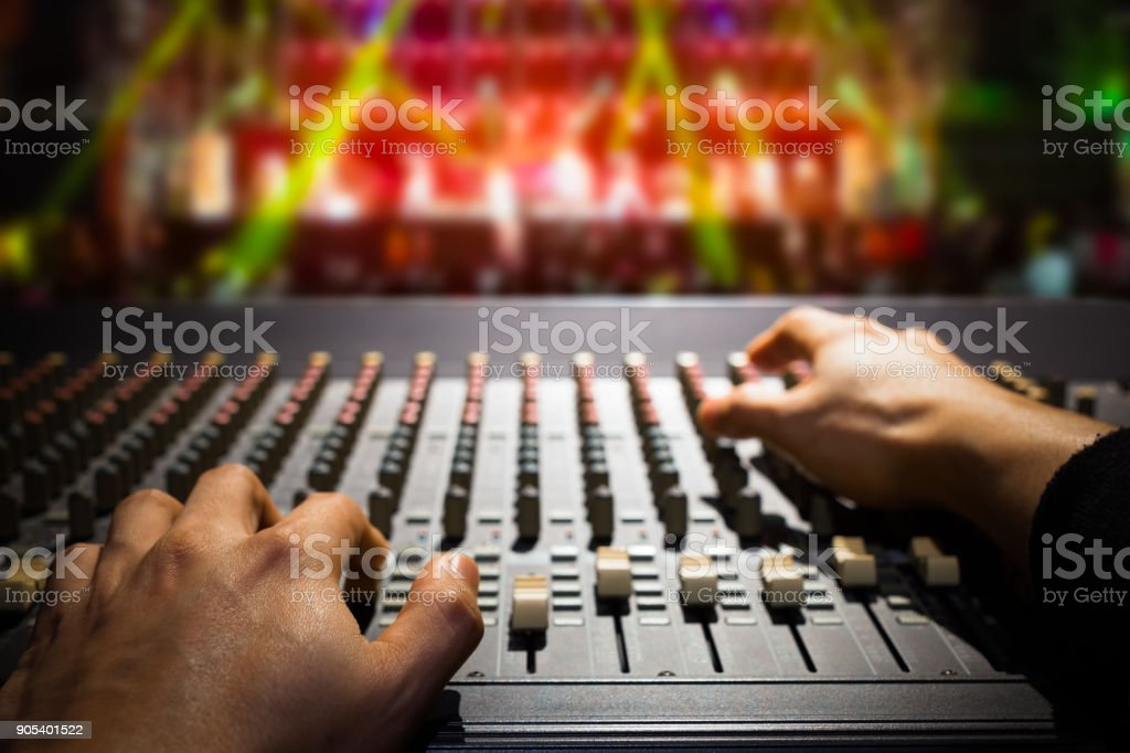 sound engineer hands working on sound mixer, background of concert stage stock photo
