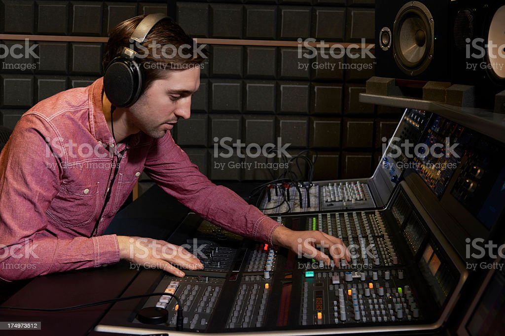 Sound engineer working at mixing desk in recording studio stock photo