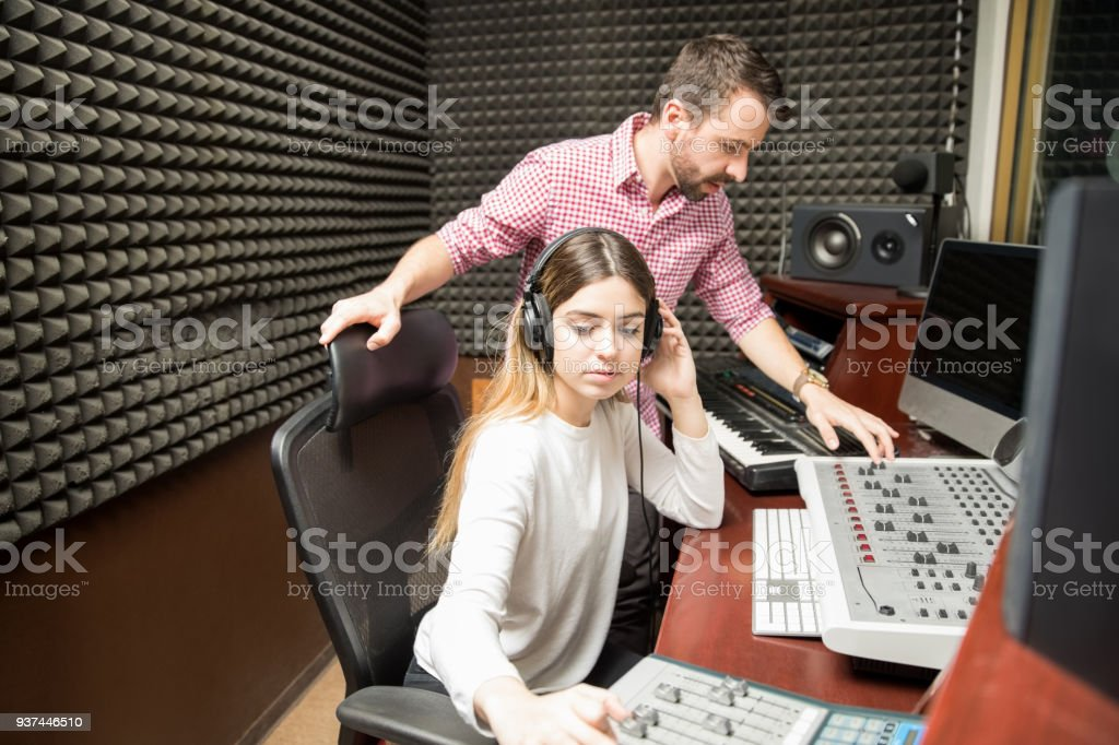 Sound engineers working in soundproof recording room stock photo