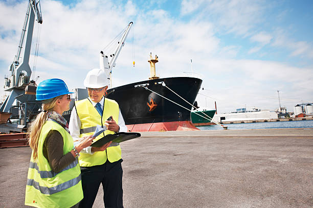 Sound management ensures fair customs trade Two dock workers holding paperwork while standing in the shipyard customs official stock pictures, royalty-free photos & images