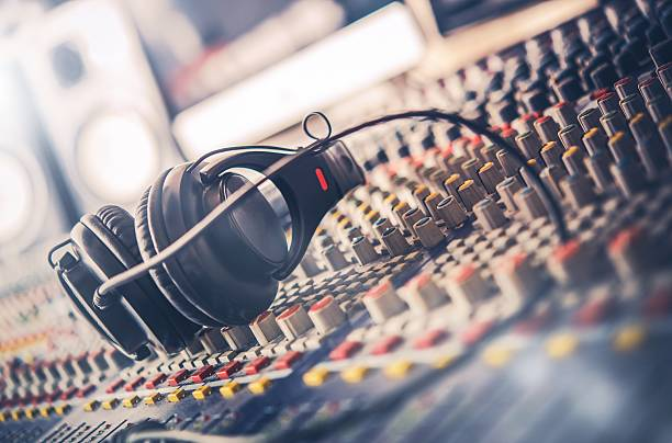 Sound Mastering Mixer Mixer and Professional Headphones in the Recording Studio. Sound Mixing Desk. Sound Mastering For Radio and TV Broadcast. sound mixer stock pictures, royalty-free photos & images